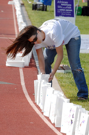 Lisa Davis places luminarias around the track during the Broomfield Relay for Life at Holy Family High School on Saturday. Some of the luminarias had cans of food placed in the for weights. The food will be donated to Broomfield FISH.<br /> June 10, 2011<br /> staff photo/David R. Jennings