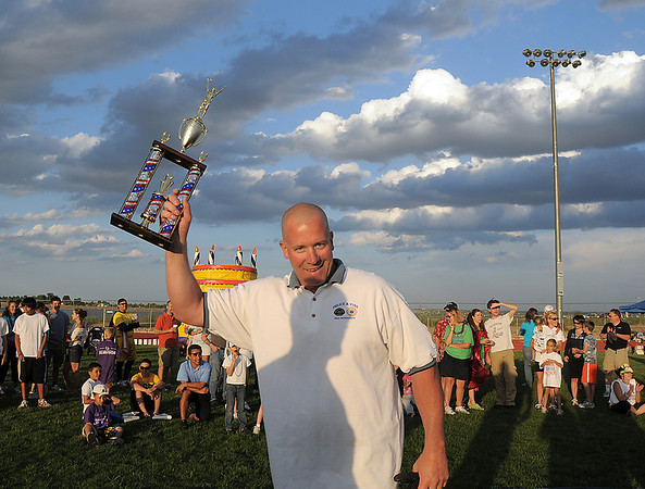 Broomfeild Police commander Cory Amen holds up a trophy after  winning the fire vs. police tug of war during the Broomfield Relay for Life at Holy Family High School on Saturday.<br /> June 10, 2011<br /> staff photo/David R. Jennings