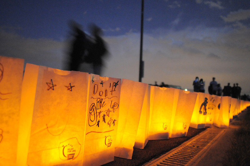 Walkers go past lit luminarias  during the luminaria ceremony at the Broomfield Relay for Life at Holy Family High School on Saturday.<br /> June 10, 2011<br /> staff photo/David R. Jennings