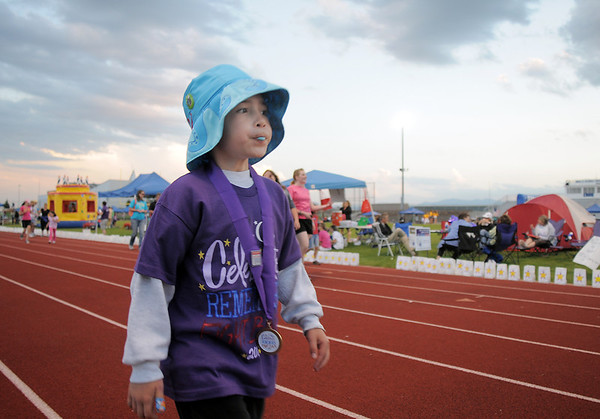 Cancer survivor Addison Kleinhans, 6, walks around the track chewing gum during the Broomfield Relay for Life at Holy Family High School on Saturday.<br /> June 10, 2011<br /> staff photo/David R. Jennings