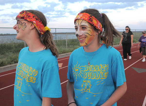 Shaneann Fross, 13, left, and Emma Stokes, 13, walk the track after having their faces painted during the Broomfield Relay for Life at Holy Family High School on Saturday.<br /> June 10, 2011<br /> staff photo/David R. Jennings