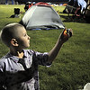 Frank Herman, 4, perpares to place an electric candle into a luminaria during the Broomfield Relay for Life at Holy Family High School on Saturday.<br /> June 10, 2011<br /> staff photo/David R. Jennings