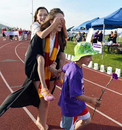 Madeline Kleinhans, 10, left, covers Rachel Kois' eyes while walking with cancer survivor Addison Kleinhans, 8, carries  during Friday's Broomfield Relay For Life at Holy Family High School.<br /> June 8, 2012 <br /> staff photo/ David R. Jennings