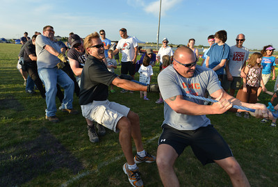 The Broomfield Police tug-of-war team pulls against the North Metro Fire Rescue team during Friday's Broomfield Relay For Life at Holy Family High School. June 8, 2012  staff photo/ David R. Jennings