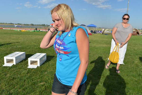 Ashley Ahrens, left, walks of the field crying after releasing doves with Julie Mensing in memory of their mothers to begin Friday's Broomfield Relay For Life at Holy Family High School.<br /> June 8, 2012 <br /> staff photo/ David R. Jennings