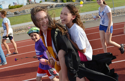 Rachel Kois carries Madeline Kleinhans, 10, around the track with Madeline's brother Addison, 8, left,a cancer survivor during Friday's Broomfield Relay For Life at Holy Family High School. June 8, 2012  staff photo/ David R. Jennings