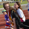 Rachel Kois carries Madeline Kleinhans, 10, around the track with Madeline's brother Addison, 8, left,a cancer survivor during Friday's Broomfield Relay For Life at Holy Family High School.<br /> June 8, 2012 <br /> staff photo/ David R. Jennings