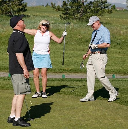 Lynn Johnson, left, Tamara Stubbs and Dan Brennan celebrate after making a putt during the Broomfield Rotary seventh annual Frank Varra Golf Tournament on Monday, May 24, 2010, at Broadlands Golf Club. Photo by Matt Kelley/For the Enterprise