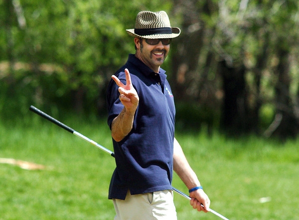 Firefighter Charles Maxwell gives the victory sign after making a successful putt on the 17th hole during the Broomfield Evening Rotary Club's Frank Varra Memorial  Broomfield Police and North Metro Fire District Benefit Golf Tournament at the Broadlands Golf Course on Monday.<br /> May 23, 2011<br /> staff photo/David R. Jennings