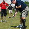 Paul Derda, right, makes a putt on the 18th green while Bill Ayers and Nick Walseth watch during the Broomfield Evening Rotary Club's Frank Varra Memorial  Broomfield Police and North Metro Fire District Benefit Golf Tournament at the Broadlands Golf Course on Monday.<br /> May 23, 2011<br /> staff photo/David R. Jennings