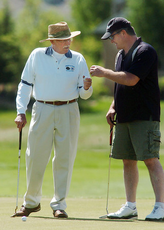 Carl Sauerland, left, chats with Ed Hedstrom while preparing to putt on the 8th hole during the Broomfield Evening Rotary Club's Frank Varra Memorial  Broomfield Police and North Metro Fire District Benefit Golf Tournament at the Broadlands Golf Course on Monday.<br /> May 23, 2011<br /> staff photo/David R. Jennings