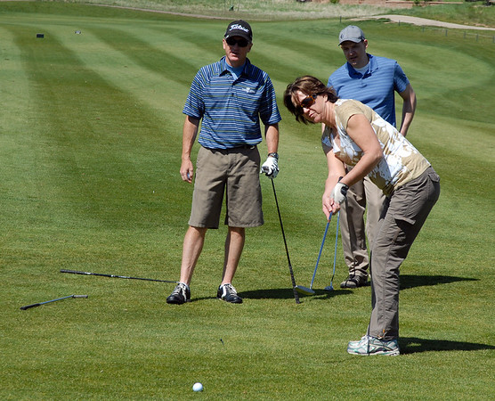 Tami Yellico putts while Dave Shinneman, left, and Bernie Block watch during the Broomfield Evening Rotary Club's Frank Varra Memorial  Broomfield Police and North Metro Fire District Benefit Golf Tournament at the Broadlands Golf Course on Monday.<br /> May 23, 2011<br /> staff photo/David R. Jennings