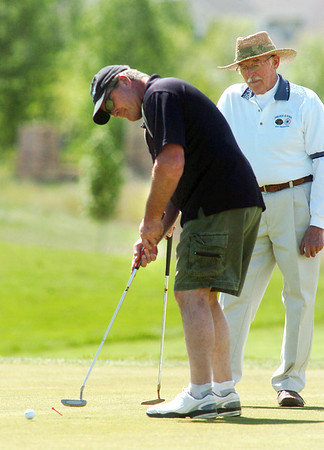 Ed Hedstrom putts while Carl Sauerland watches on the 7th green during the Broomfield Evening Rotary Club's Frank Varra Memorial  Broomfield Police and North Metro Fire District Benefit Golf Tournament at the Broadlands Golf Course on Monday.<br /> May 23, 2011<br /> staff photo/David R. Jennings