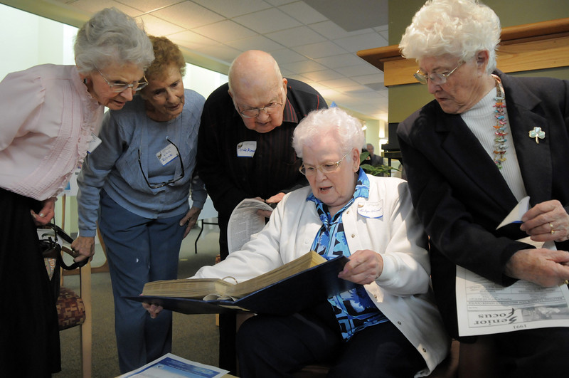 Ann Robinson, left, Lois Buse, Dale Munson with Evelyn Kanost and Pat Blackburn look through a scrapbook covering the early years of the senior center during the 20th anniversary celebration of the Broomfield Senior Center on Sunday.<br /> March 20, 2011<br />  staff photo/David R. Jennings