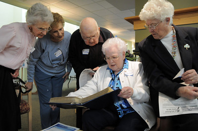 Ann Robinson, left, Lois Buse, Dale Munson with Evelyn Kanost and Pat Blackburn look through a scrapbook covering the early years of the senior center during the 20th anniversary celebration of the Broomfield Senior Center on Sunday. March 20, 2011  staff photo/David R. Jennings