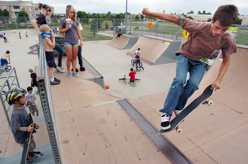 Kyle Martin, 16, right, performs a trick on his skate board while others watch at the Broomfield Skate Park on Tuesday.<br /> <br /> <br /> August 4, 2009<br /> staff photo/David R. Jennings