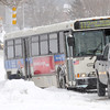 First Transit employees work on getting an RTD bus unstuck along Midway Blvd.  near Garden Center during the February 3rd snowstorm.<br /> February 3, 2012<br /> staff photo/ David R. Jennings