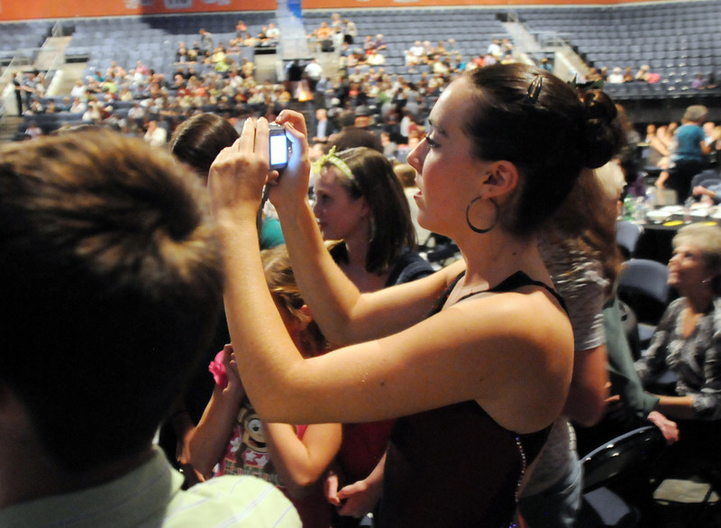 Dancer Sophie Payannet takes pictures of FACE singing while the votes are tallied during Dancing with the Broomfield Stars on Thursday at 1stBank Center.<br /> <br /> September 23, 2010<br /> staff photo/David R. Jennings