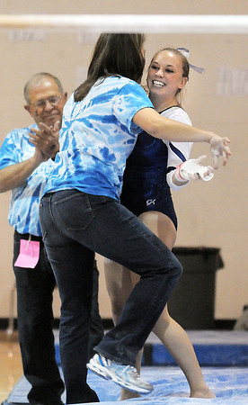 Allie Burgess, Broomfield, celebrates her performance on the bars with coach Erik Taga during the state 5A gymnastics meet at Thornton High School on Friday.<br /> <br /> November 4, 2011<br /> staff photo/ David R. Jennings