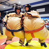 Teachers Kevin Stirling, left, Sumo wrestles Kailen Eichhorn with junior Jeff Tapia refereeing during the Teach Olympics competition at Broomfield High School on Wednesday.<br /> .<br /> <br /> <br /> November 4, 2009<br /> Staff photo/David R. Jennings