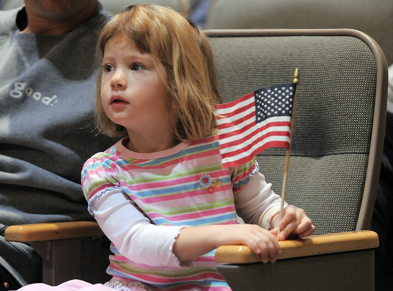 Grace Fossell, 4, holds a flag while watching the Veterans Day Observance sponsored by the Broomfield Veterans Memorial Museum at Broomfield High School on Thursday.<br /> November 11, 2010<br /> staff photo/David R. Jennings