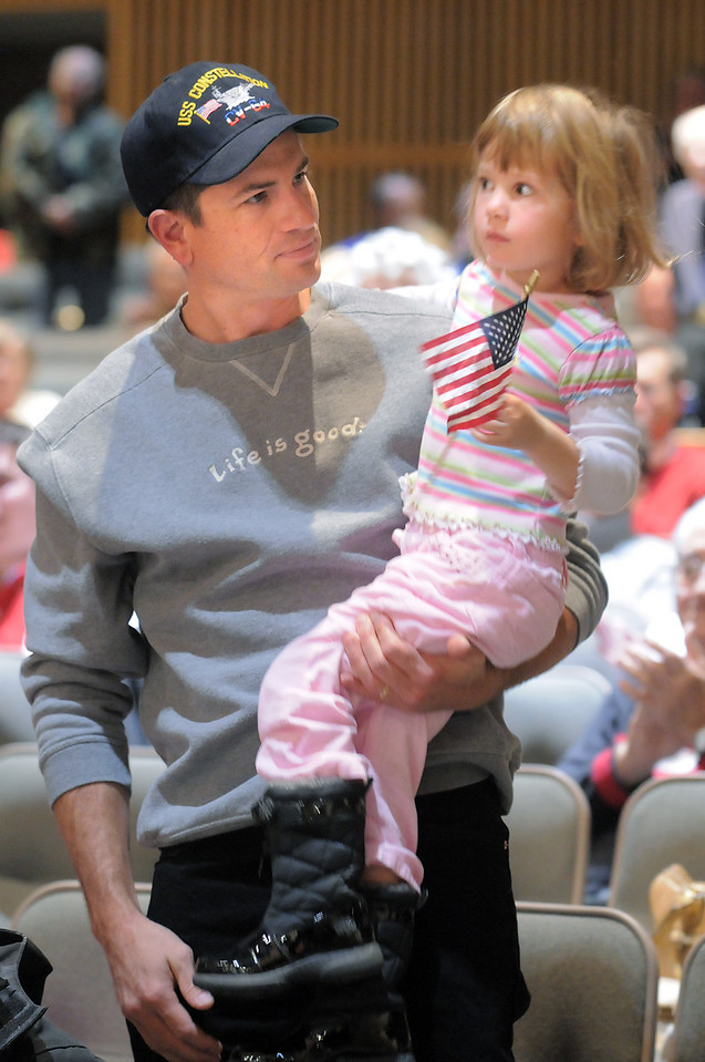 U.S. Navy veteran Robert Fossell and his daughter Grace, 4, watch the ceremonies during the Veterans Day Observance sponsored by the Broomfield Veterans Memorial Museum at Broomfield High School on Thursday.<br /> November 11, 2010<br /> staff photo/David R. Jennings