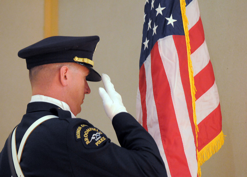 Broomfield Police Honor guard member officer Todd Dahlbach salutes while presenting the U.S. Flag during the Veterans Day Observance sponsored by the Broomfield Veterans Memorial Museum at Broomfield High School on Thursday.<br /> November 11, 2010<br /> staff photo/David R. Jennings