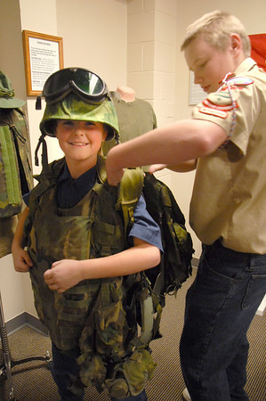 Alex Pearson, 10, left, tries on Vietman battle gear with the help of Dalton Rezac, 14, at the Broomfield Veteran's Museum on Wednesday.<br /> <br /> November 11, 2009<br /> Staff photo/David R. Jennings