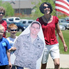 Lisa Smith, right, her son Brenden, 8, center, carrying a to scale photograph of his father, USAF Lt. Col. Bill Smith, who is currently serving in Iraq,  with frieind Jon Ducat, 8, and Brenden's, grandmother, during the Broomfield Veterans Memorial Museum's Memorial Day Picnic on Monday at the Broomfield County Commons Park . Lisa Smith, from Parker, and her family, carry her husband's picture around and takes pictures with the photograph at various events including a graduation so he can see where he's been when he returns from Iraq. <br /> May 31, 2010<br /> Staff photo/ David R. Jennings