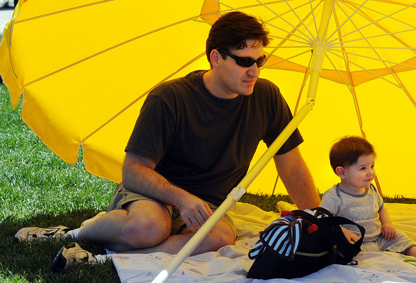 Matthew Zotter and his son Desmond, 10 months-old, sit under a large umberella  during the Broomfield Veterans Memorial Museum's Memorial Day Picnic on Monday at the Broomfield County Commons Park .<br /> May 31, 2010<br /> Staff photo/ David R. Jennings