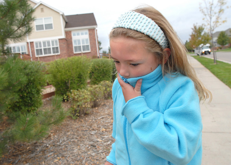Fiona Kennedy, 7, shields her face from the cold while walking to Aspen Creek K-8  for Walk to School Day on Wednesday.<br /> <br /> October 6, 2010<br /> staff photo/David R. Jennings