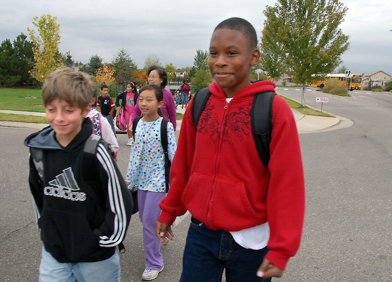 Isaac Sucik, 11, left, and Lynn Busby, 10 walk along ASpen Creek Dr. to Aspen Creek School for Walk to School Day on Wednesday.<br /> <br /> October 6, 2010<br /> staff photo/David R. Jennings