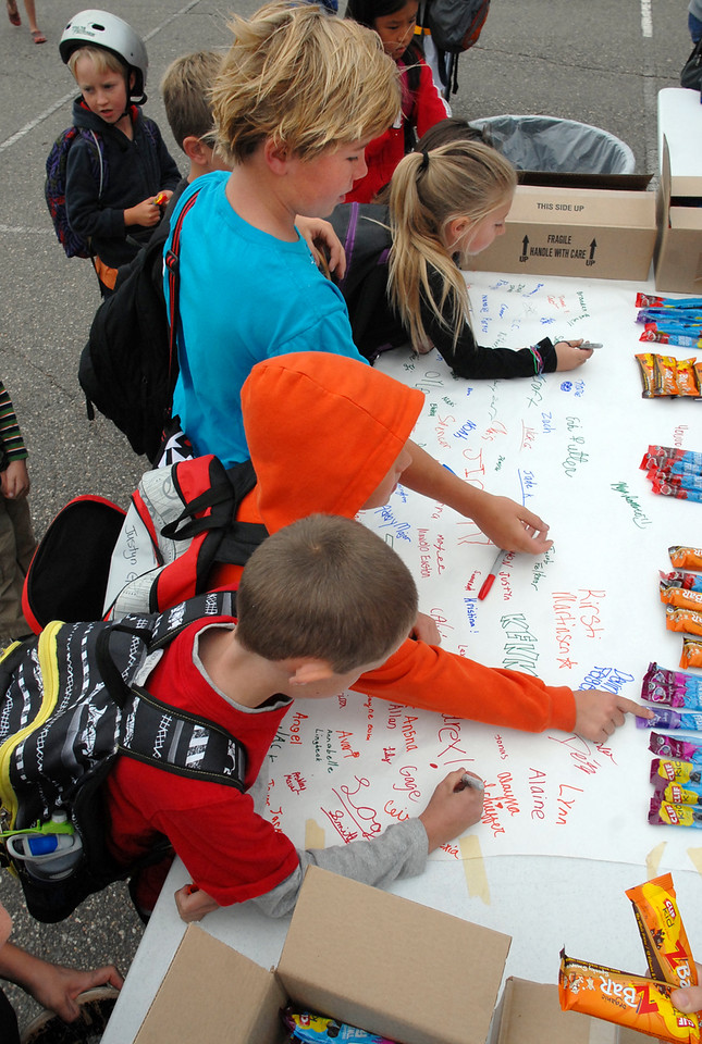 Aspen Creek students sign a poster and receive a nutritional bar  for Walk to School Day on Wednesday.<br /> <br /> October 6, 2010<br /> staff photo/David R. Jennings