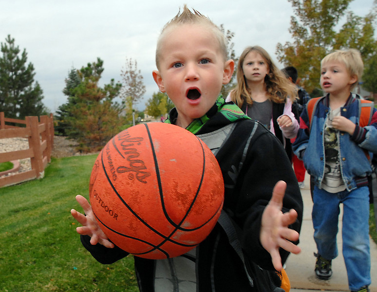 Aiden Mayo, 6, juggles his basketball while walking to Aspen Creek K-8 during Walk to School Day on Wednesday.<br /> <br /> October 6, 2010<br /> staff photo/David R. Jennings