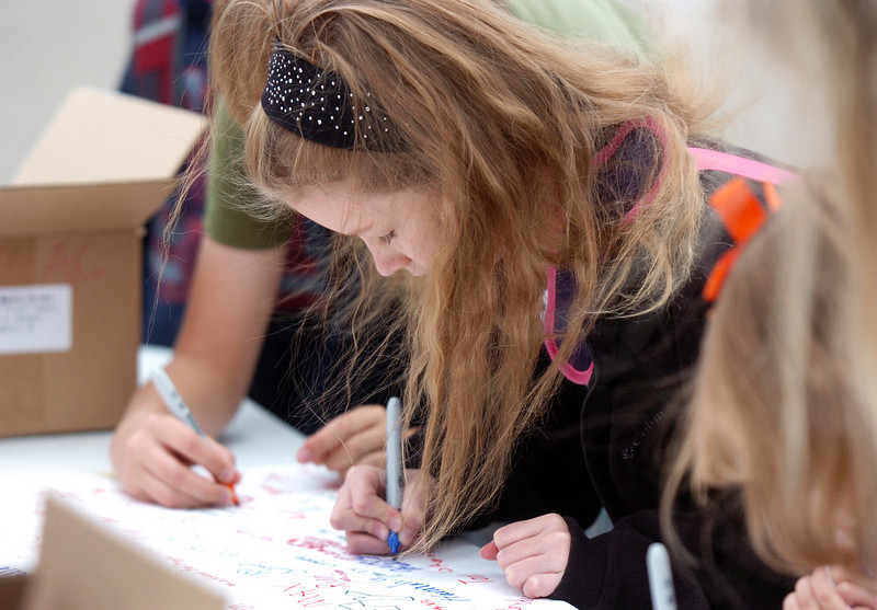 Abby Nelson, 9, signs a poster after walking  to Aspen Creek K-8 School for Walk to School Day on Wednesday.<br /> <br /> October 6, 2010<br /> staff photo/David R. Jennings