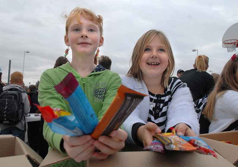 Sonja Schmoyer, 9, left, and Hannah Campbell, 8, hand out nutrition bars to students who walked to Aspen Creek K-8 School for Walk to School Day on Wednesday.<br /> <br /> October 6, 2010<br /> staff photo/David R. Jennings