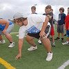 Instructors Payton Bane, left, and Colin Eakes go into their stance as they demonstrate a  blocking drill to participants during Tuesday's Broomfield High School Youth Football Camp at Elizabeth Kennedy Stadium.<br /> <br /> July 28,2009<br /> staff photo/David Jennings