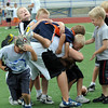 Instructor Jake Wheeler, center,  is mobbed by 2nd graders during Tuesday's Broomfield High School Youth Football Camp at Elizabeth Kennedy Stadium.<br /> <br /> July 28,2009<br /> staff photo/David Jennings