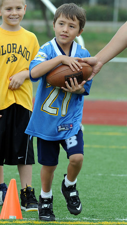Payton Rupp, 8, takes a handoff to run a route during Tuesday's Broomfield High School Youth Football Camp at Elizabeth Kennedy Stadium.<br /> <br /> July 28,2009<br /> staff photo/David Jennings