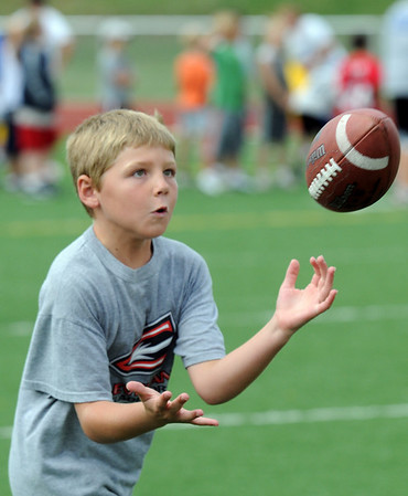 Ryan Ruger, 8, catches a pass from an instructor during Tuesday's Broomfield High School Youth Football Camp at Elizabeth Kennedy Stadium.<br /> <br /> July 28,2009<br /> staff photo/David Jennings