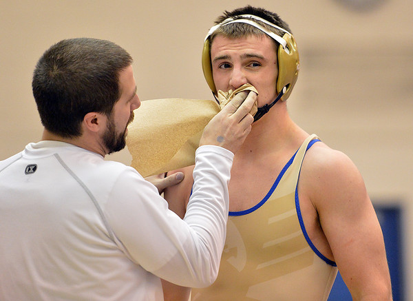 Broomfield's head coach Joseph Pereira wipes blood from Zach Stodden while wrestling Valor Christian's Chaz Polson in the 170 pound 4A region 3 match at Mullen High School on Saturday.<br /> February 16, 2013<br /> staff photo/ David R. Jennings