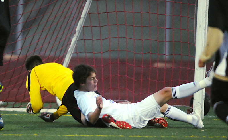 Landon Roos  ,Broomfield, collides with Harrison's goalie Daniel Cordero to score during the game on Tuesday at Elizabeth Kennedy Stadium.<br /> <br /> October 27, 2009<br /> Staff photo/David R. Jennings