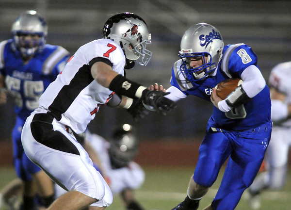 Broomfield's quarterback Aric Kaiser tries to avoid being tackled by Kyle Klein, Loveland during Friday's game at Elizabeth Kennedy Stadium.<br /> <br /> October 23, 2009<br /> Staff photo/David R. Jennings