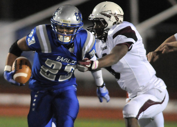 Broomfield's Jose Faire carries the ball downfield avoiding a tackle by Cheyenne Mountain's Donivan Harville during Friday's first round state 4A playoff game at Elizabeth Kennedy Stadium.<br /> <br /> November 11, 2011<br /> staff photo/ David R. Jennings