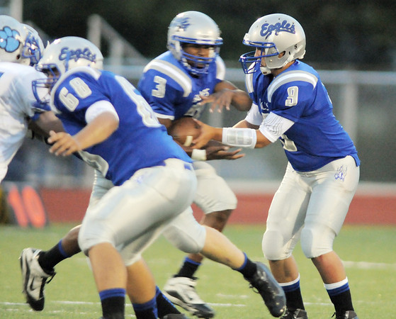 Broomfield's Sean Robnett takes a hand off from quarterback Angelo Perez during Friday's game against Fruita Monument at Elizabeth Kennedy Stadium.<br /> <br /> August 26, 2011<br /> staff photo/ David R. Jennings