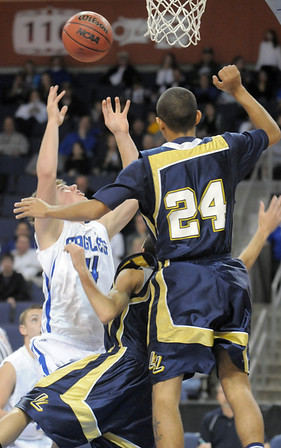 Eagle's Aric Kaiser shoots past Marcus Riddick and Keenan Creath during Saturday's cross town boys game at the 1stBank Center.<br /> January 8, 2011<br /> staff photo/David R. Jennings
