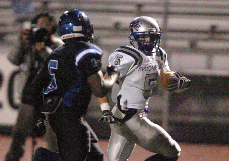 Broomfield's Dan Geubelle runs the ball to the end zone for a touchdown while Longmont's Mark Lipford approaches for a tackle during Friday's game at Everly-Montgomery Field in Longmont.<br /> <br /> October 22, 2010<br /> staff photo/David R. Jennings
