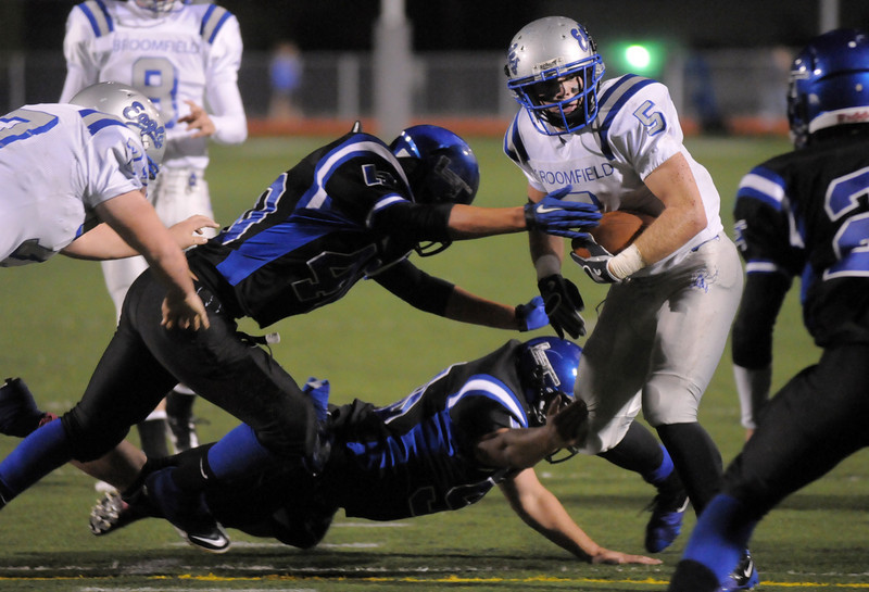 Broomfield's Dan Geubelle carries the ball trying to avoid the tackle attempt by Longmont's Chris Chacon and Chase Hunnel during Friday's game at Everly-Montgomery Field in Longmont.<br /> <br /> October 22, 2010<br /> staff photo/David R. Jennings
