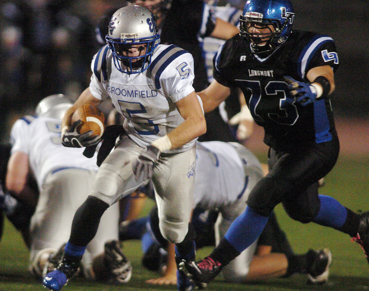 Broomfield's Dan Geubelle carries the ball past Matt Cirbo, Longmont during Friday's game at Everly-Montgomery Field in Longmont.<br /> <br /> October 22, 2010<br /> staff photo/David R. Jennings