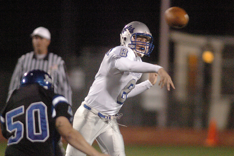 Broomfield's quarterback Aric Kaiser passes the ball as Longmont's Vaun Kipper approaches during Friday's game at Everly-Montgomery Field in Longmont.<br /> <br /> October 22, 2010<br /> staff photo/David R. Jennings